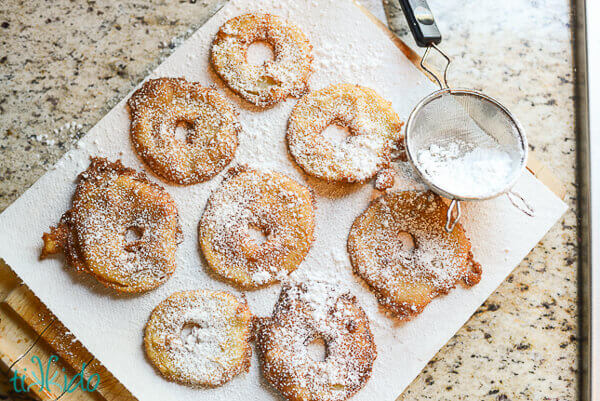 Apple fritter rings dusted with powdered sugar