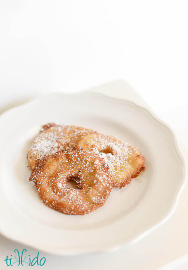 Apple fritter rings dusted with powdered sugar on a white plate.