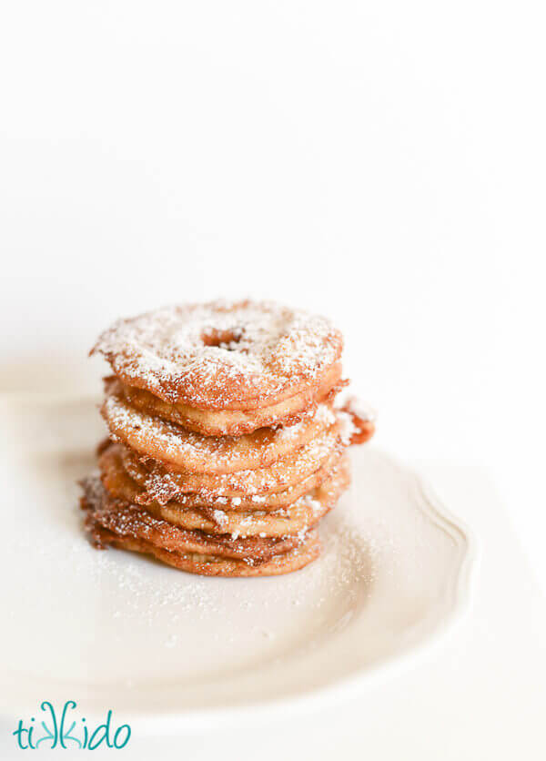 Apple fritter rings dusted with powdered sugar and stacked on a white plate.