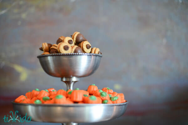Chocolate acorns in a tiered serving tray with candy corn pumpkin candies.
