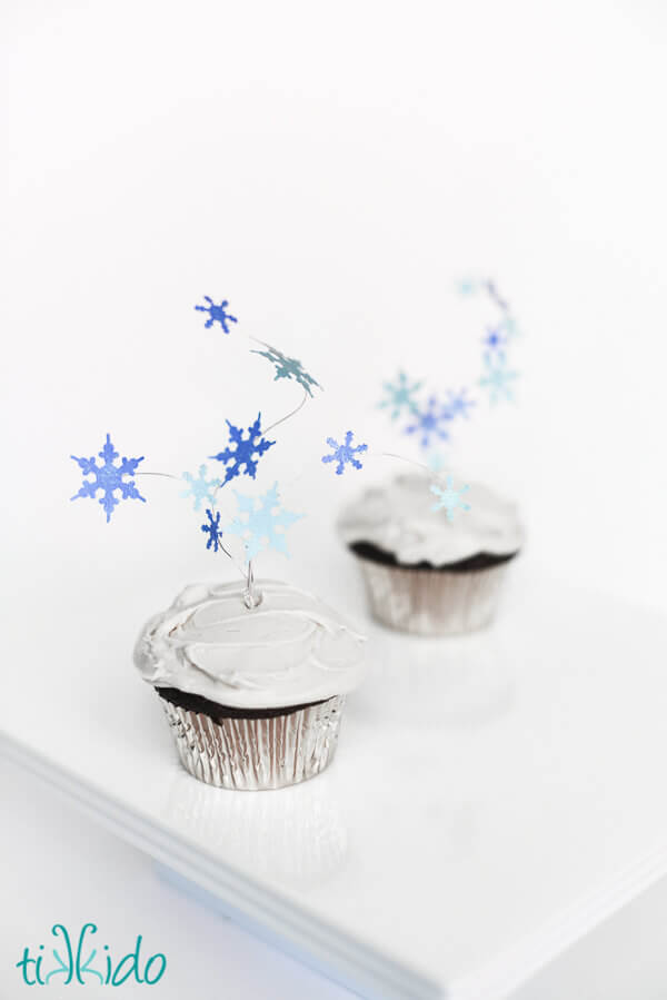 Two cupcakes topped with flying snowflakes cupcake toppers.