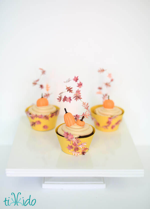 Three cupcakes topped with cupcake toppers that look like swirling fall leaves.