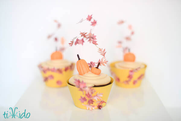 Three cupcakes topped with gum paste pumpkins and fall leaf cupcake toppers.