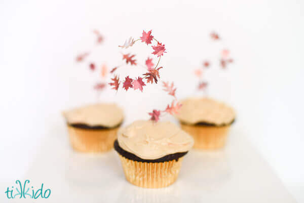 three cupcakes topped with swirling fall leaf cupcake toppers.