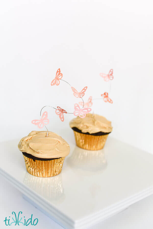 Two cupcakes topped with flying butterfly cupcake toppers