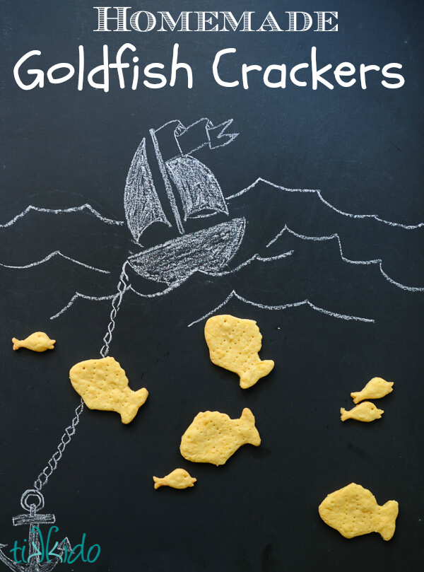 Homemade goldfish crackers on a black chalkboard background with a drawing of a boat and ocean waves.