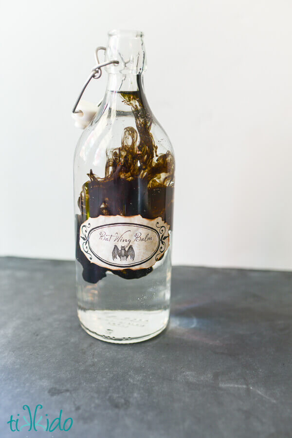 Halloween potion bottle full of water with black food coloring being added.