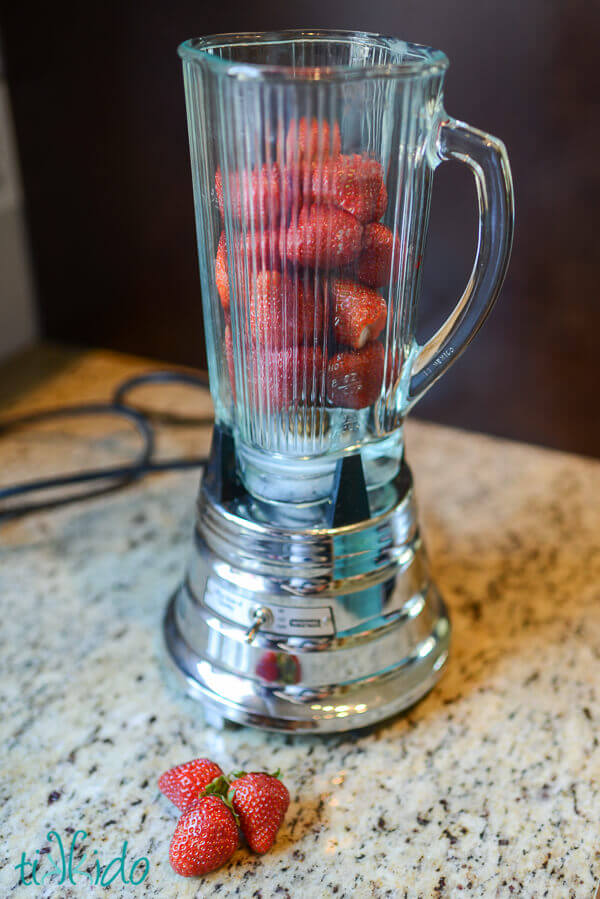 Strawberries in a waring blender on a granite counter.
