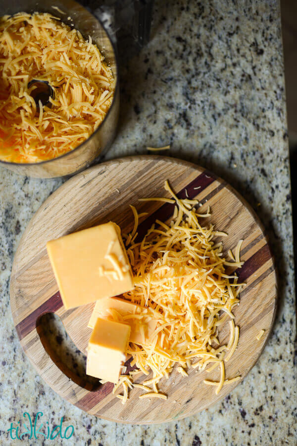 Block of cheese partially shredded on a wooden cutting board for making Cheese crackers.
