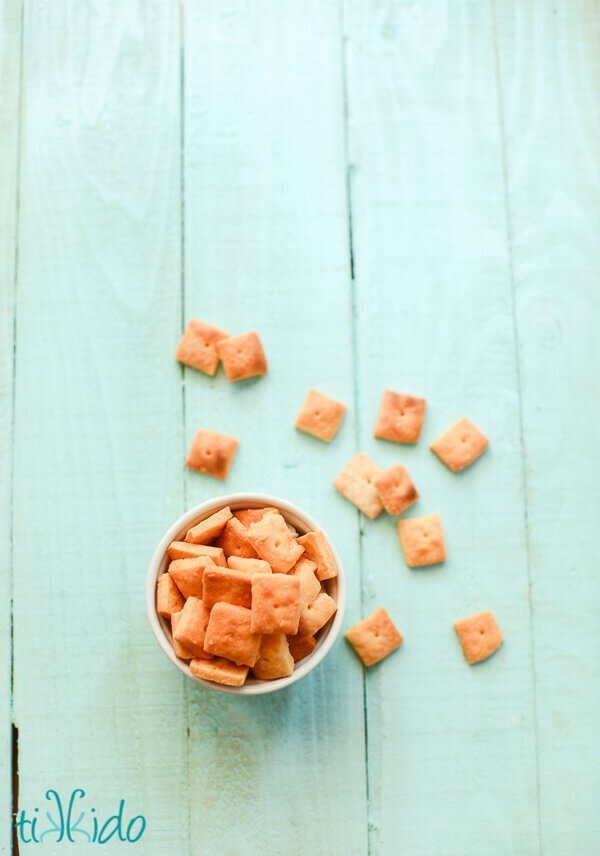 Homemade cheese crackers in a bowl on an aqua wooden background.