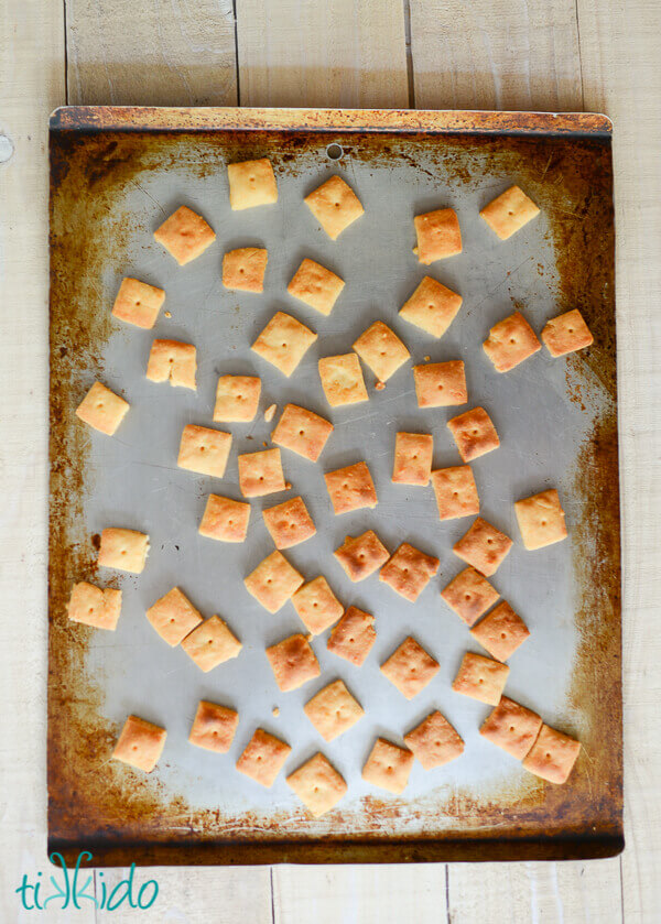 Homemade cheese crackers baked on a cookie sheet.
