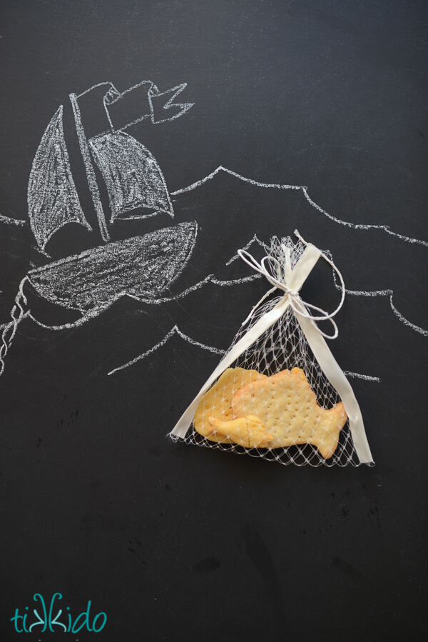 Homemade goldfish crackers in a net bag on a black chalkboard drawn with a boat and ocean waves.