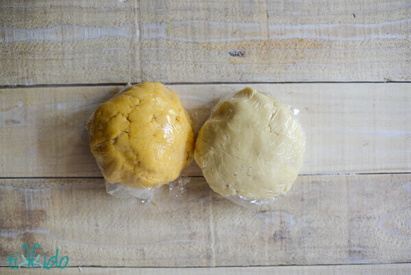Two balls of homemade cheese cracker dough on a wooden surface.