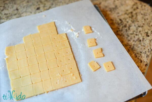 Square shaped Cheese crackers cut on a sheet of parchment paper.