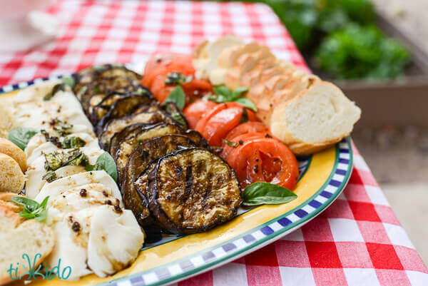 Grilled, marinated, Italian eggplant antipasto plate with sliced tomatoes, fresh mozzarella, and bread.