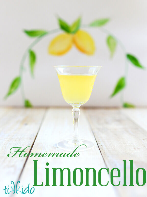 Small glass of limoncello with a painted lemon watercolor backdrop behind.