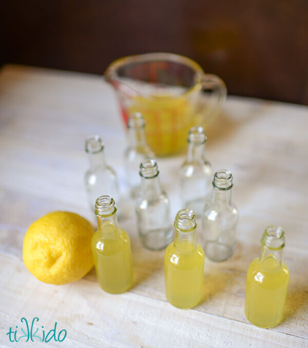 Homemade limoncello being bottled in miniature, individual serving size bottles.