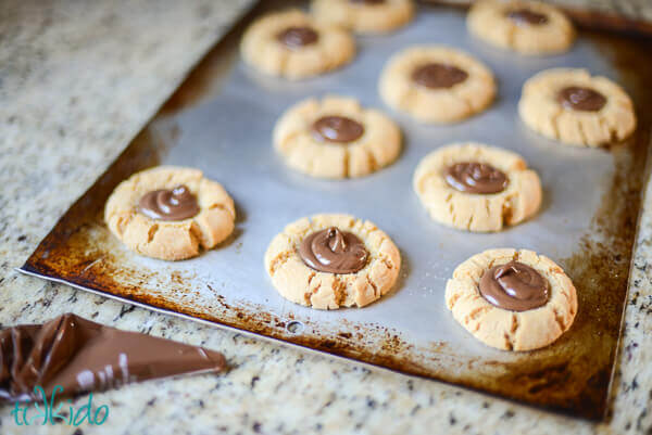 Peanut Butter Nutella Thumbprint Cookies on a baking sheet.