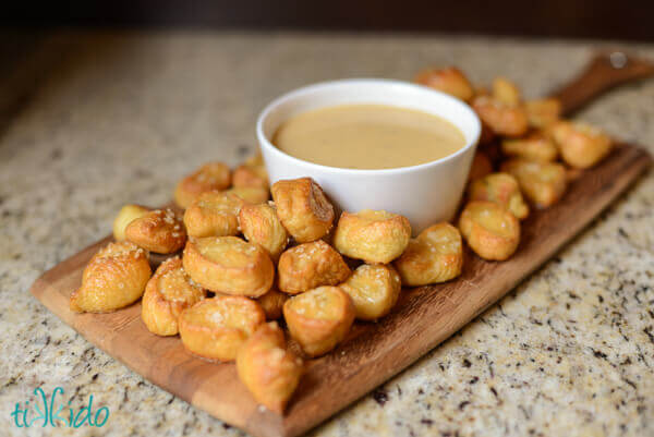 White bowl of beer cheddar sauce surrounded by homemade pretzel bites, displayed on a wooden cutting board on a granite counter.