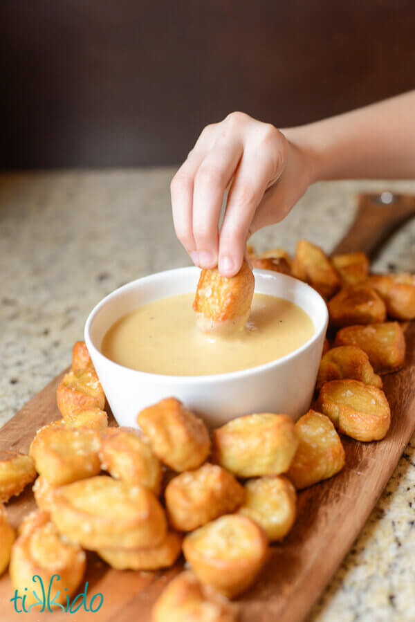Hand dipping a homemade pretzel bite into a white bowl full of homemade beer cheddar dipping sauce.