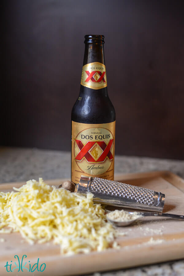 Bottle of Dos Equis beer, surrounded by a nutmeg grater, a heaping teaspoon of flour, and a pile of shredded white cheddar cheese.