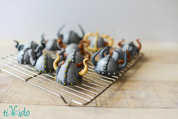 Viking helmet cupcake toppers on a drying rack.