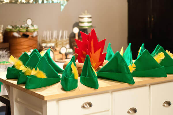 Green Felt Peter Pan Hats With Yellow Feathers Arranged In A Circle Around Campfire