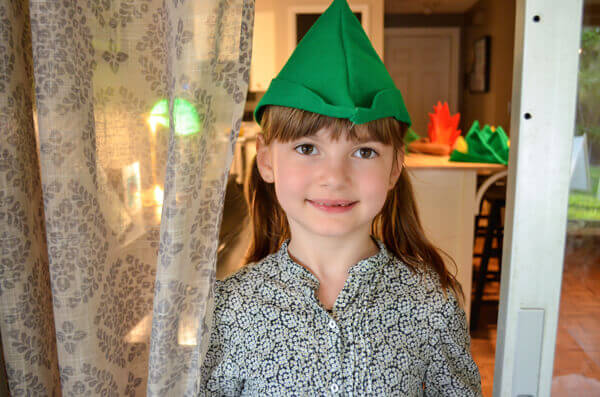 Little Girl Wearing A Green Felt Peter Pan Hat