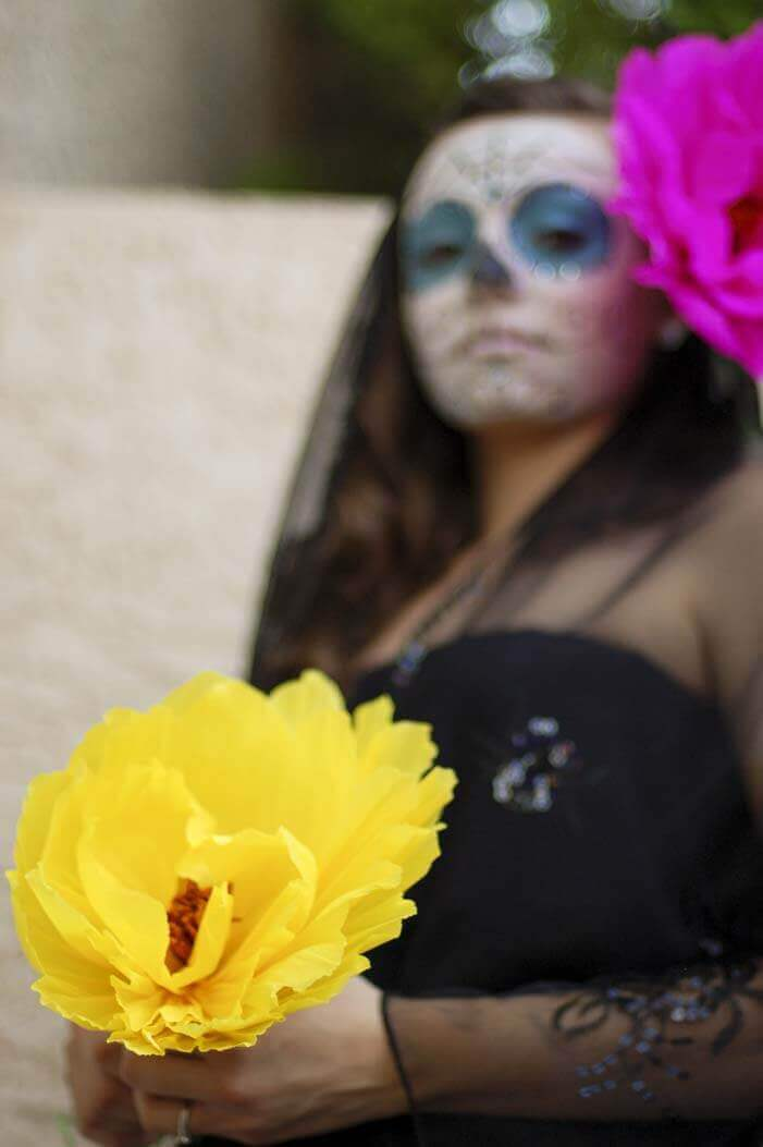 Woman in Dia de los Muertos makeup and a black dress holding a giant yellow tissue paper flower.