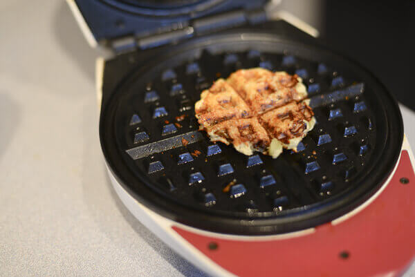 Eggplant slice coated with parmesan cheese being cooked on a waffle iron.