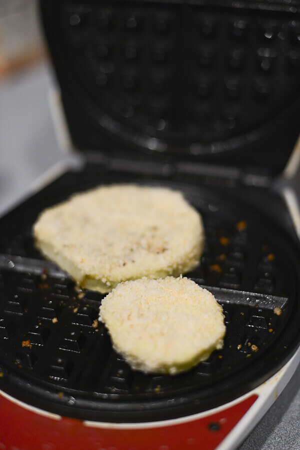 Eggplant slices coated with parmesan cheese being cooked on a waffle iron.