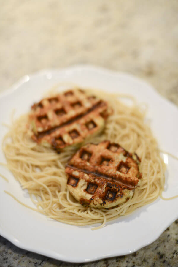 Low carb, gluten free, healthy eggplant parmesan made in a waffle iron on a bed of pasta on a white plate.