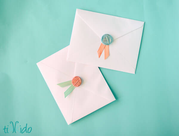 faux wax seals and ribbon decorating envelopes