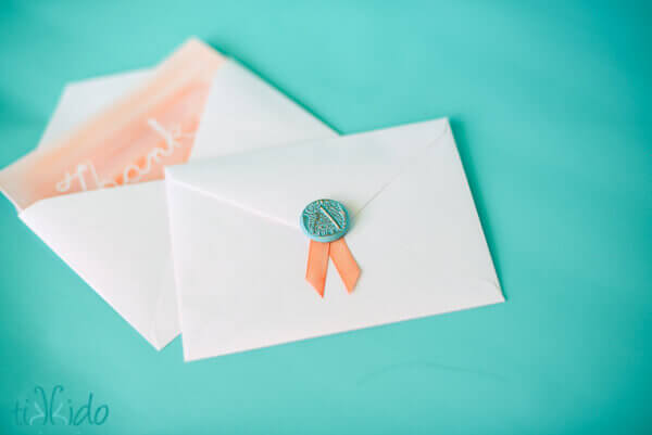 Faux wax seal and ribbon on the envelope of a thank you note.