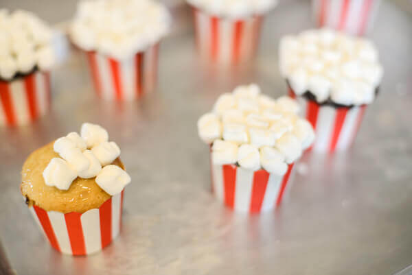 Baked Cupcakes In Red And White Baking Cups Being Covered With Mini Marshmallows
