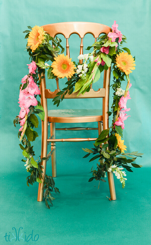 Real Flower Garland Draped On A Golden Chair Turquoise Background