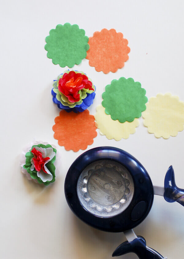 Scalloped circle paper punch and tissue paper cut into circles, some gathered into miniature Mexican tissue paper flowers.