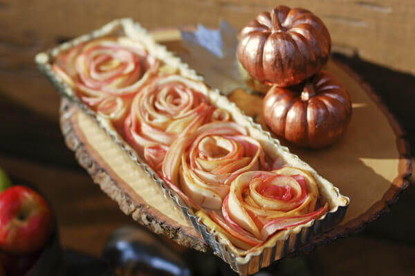 Rose Apple Pie on a wooden cake stand next to fall pumpkins.