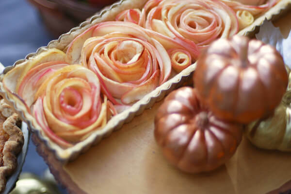 Rose Apple Pie in a rectangular pie tin, next to miniature pumpkins.