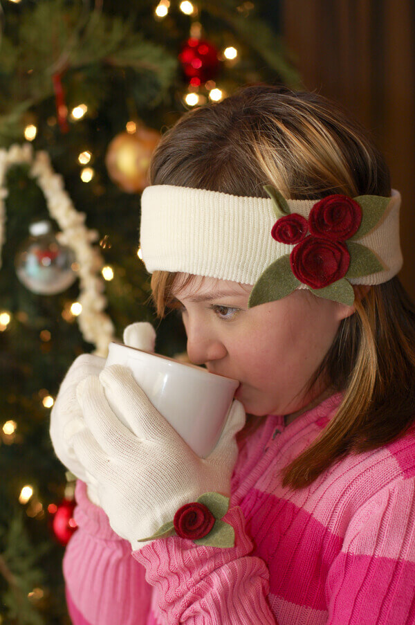 Girl sipping hot chocolate in front of a Christmas tree