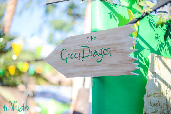 Faux wood sign pointing the way to the Green Dragon at the Lord of the Rings birthday