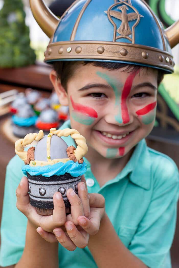 Boy wearing a viking helmet and holding a viking cupcake topped with a gum paste viking helmet.