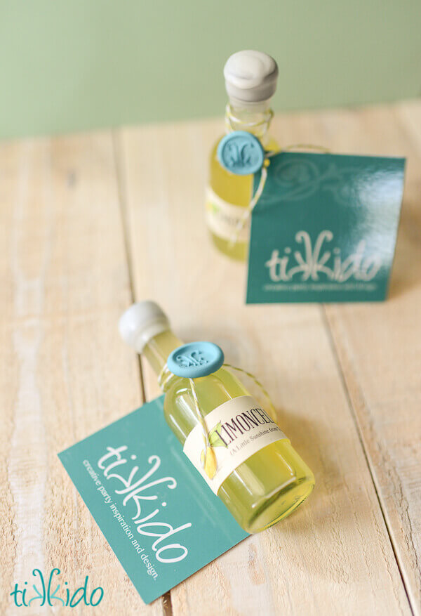 Two individual serving sized bottles of homemade limoncello sealed with wax and a wax seal, tied with a Tikkido business card.