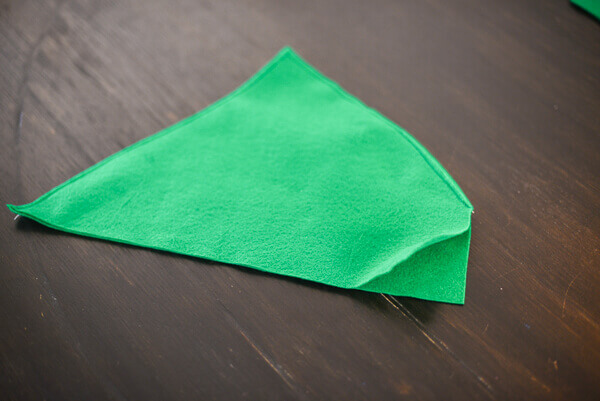 Two Pieces Of Green Felt Cut Out To Make A Peter Pan Hat And Sewn Along