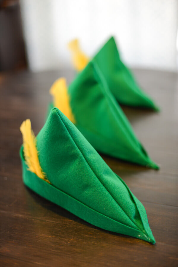 Set Of Three Green Felt Peter Pan Hats With Yellow Feathers Lined Up On A