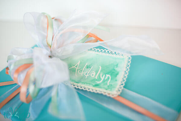 Gift wrapped in turquoise paper and finished with a bow made from painted ribbon.