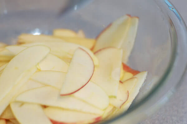 Thinly sliced apples in a clear bowl for Rose Apple Pie