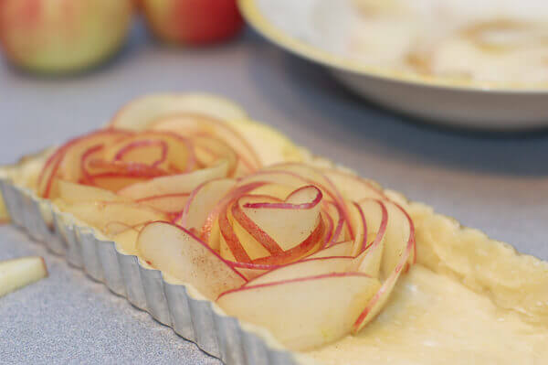 Thin slices of apples being shaped into roses for the rose apple pie.