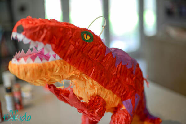 Store bought dinosaur pinata ready to be transformed into an easy DIY Dragon piñata.