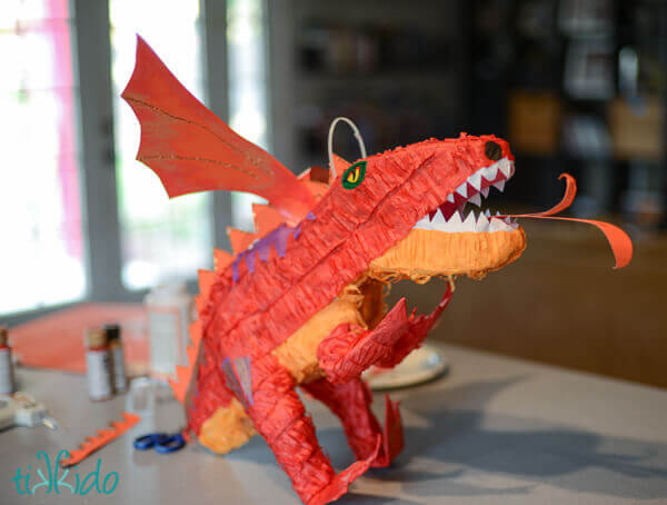 Attaching wings and other embellishments to dinosaur piñata to transform it into a DIY Dragon piñata.